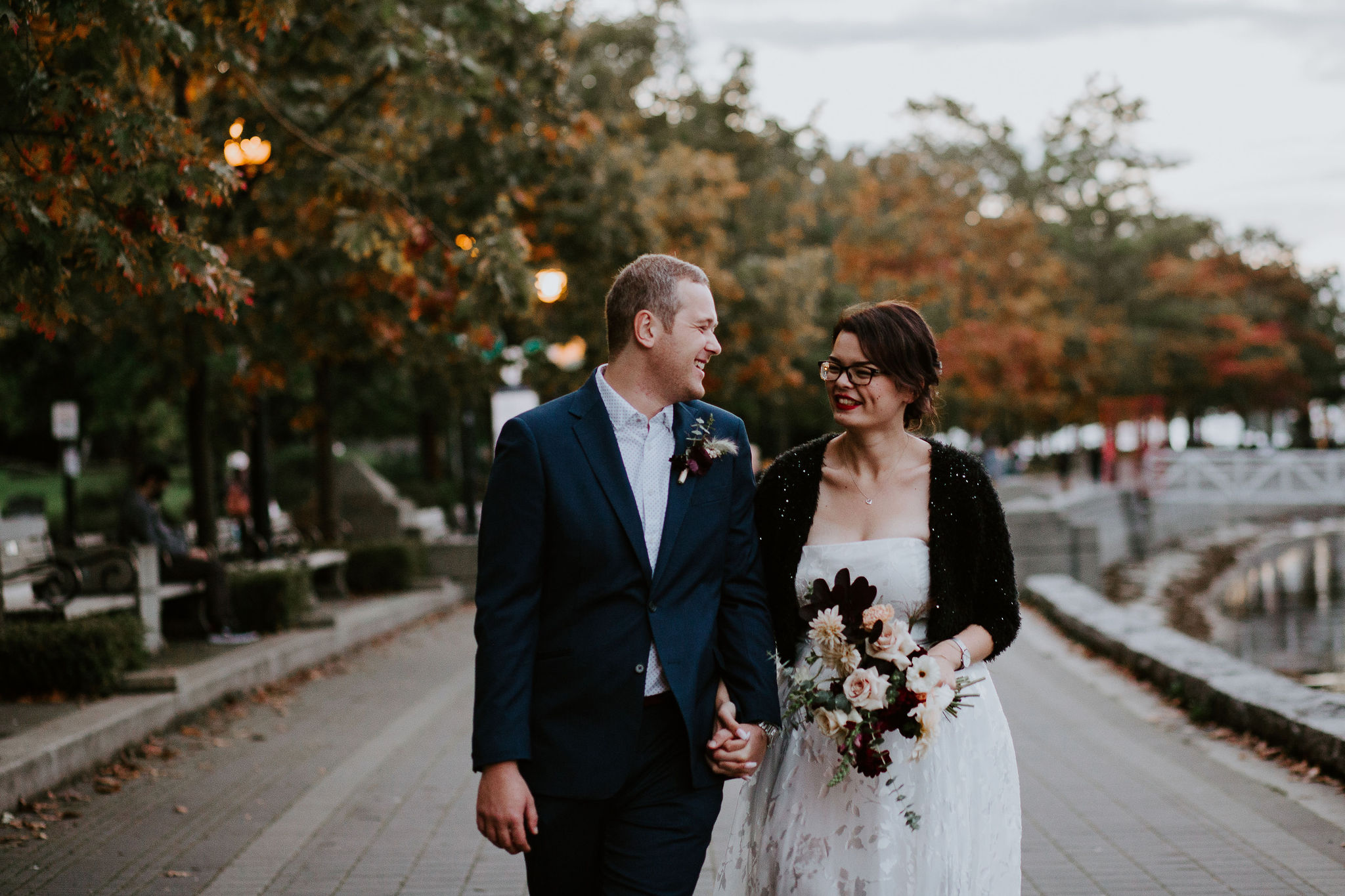 Couple walking on the Vancouver Sea Wall after their wedding
